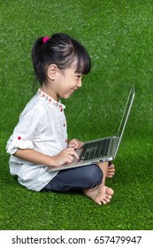 Asian Chinese little girl sitting on the grass and playing with laptop at outdoor park