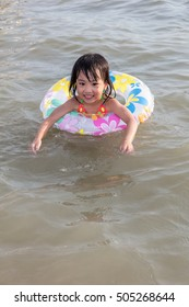 Asian Chinese little girl swimming at the seaside alone.