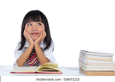 Asian Chinese little girl thinking while reading in isolated white background.