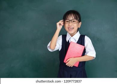 Asian Chinese little Girl in uniform standing against green blackboard in classroom