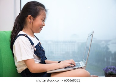 Asian Chinese little girl using laptop on the windowsill at home.