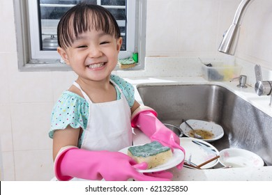 Asian Chinese little girl washing dishes in the kitchen at home