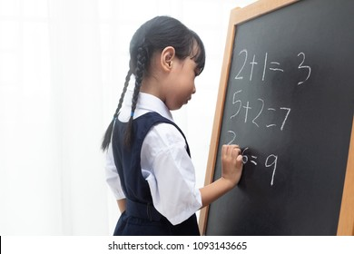 Asian Chinese little girl writing on blackboard in isolated white background