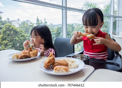 Asian Chinese little girls eating fried chicken at indoor restaurant