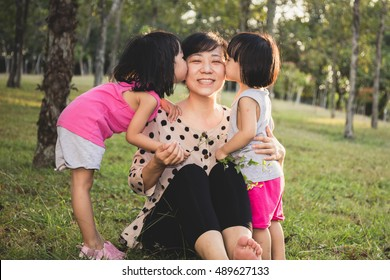 Asian Chinese Little Girls Kissing Mother at Park in the evening.
