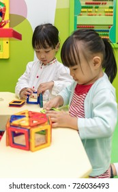 Asian Chinese little girls playing colorful magnet plastic blocks kit at indoor playground