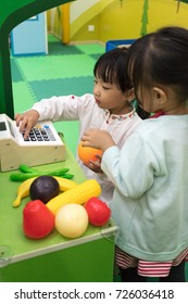 Asian Chinese little girls role-playing at fruits store at indoor playground