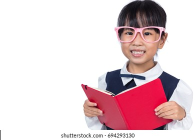 Asian Chinese little primary school girl in uniform reading book in isolated white background