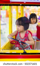 Asian Chinese Little Sister Driving Toy Bus at indoor playground.