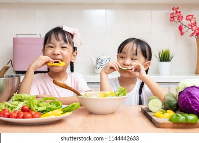 Asian Chinese little sisters eating salad in the kitchen at home