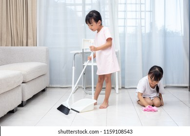 Asian Chinese little sisters helping doing cleaning at home