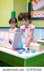 Asian Chinese little sisters role-playing at sushi store at indoor playground