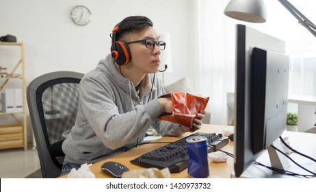 asian chinese man hand eating fast food bag potato chips with soda can while having fun leisure spend time on computer game. unhealthy junk food lifestyle concept. otaku watching anime summer break