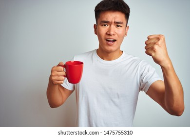 Asian chinese man holding red cup of coffee standing over isolated white background annoyed and frustrated shouting with anger, crazy and yelling with raised hand, anger concept