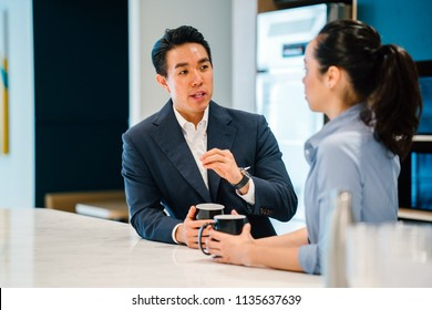 An Asian Chinese man in a suit has a discussion with his Eurasian woman colleague in an office during the day. They are both holding mugs of a hot beverage (coffee or tea) and talking.