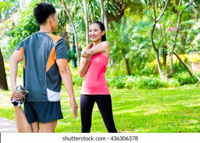 Asian Chinese man and woman stretching muscles in park for sport fitness