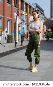 Asian Chinese model girl influencer street shot. Wearing Blue top and army green pants. Street Graffiti background.