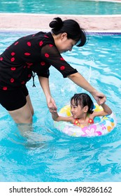 Asian Chinese Mom Teaching Little Girl Swimming At The Outdoor Pool.