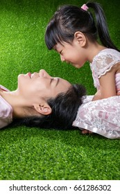 Asian Chinese mother and daughter lying on the grass looking at each other at outdoor park