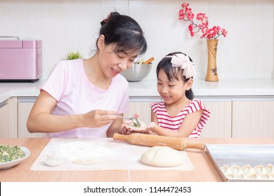 Asian Chinese mother and daughter making dumpling in the kitchen at home