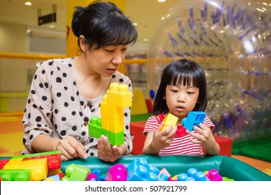 Asian Chinese mother and daughter playing blocks at indoor playground.