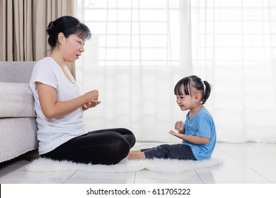 Asian Chinese mother and daughter playing rock-paper-scissors in the living room at home.