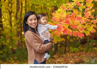Asian Chinese mother holding cute adorable  baby girl on hands in autumn fall park outdoor with yellow orange leaves trees. Halloween or Thanksgiving autumnal seasonal concept.