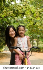 asian chinese mother teaching her daughter riding bicycle outdoor
