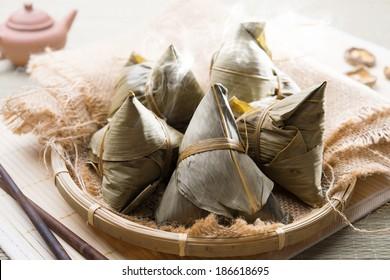 Asian Chinese rice dumplings on basket, tea at background.