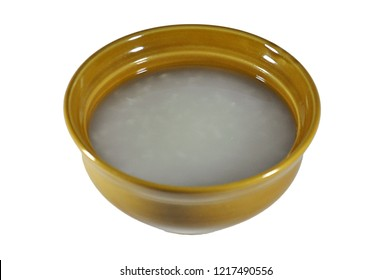 Asian or chinese style plain rice soup or boiled rice or porridge or congee in traditional ceramic bowl isolated in white background with work path ready to use or di cut