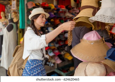 asian chinese traveler tourist shopping walking on the famous local street market looking for beautiful weave cap for friends or family in the Hong Kong vacation.