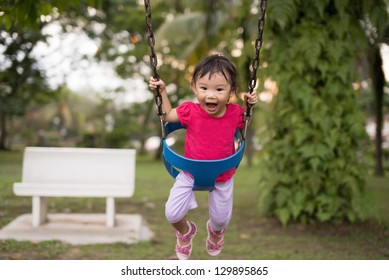 Asian Chinese two-year old girl on a swing in the playground