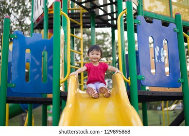 Asian Chinese two-year old girl on a slide in the playground