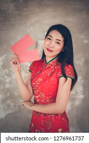 0078f3020 Asian Chinese Woman in Cheongsam Traditional Red Dress Holding Red Envelope  for Giving Ang Pao in