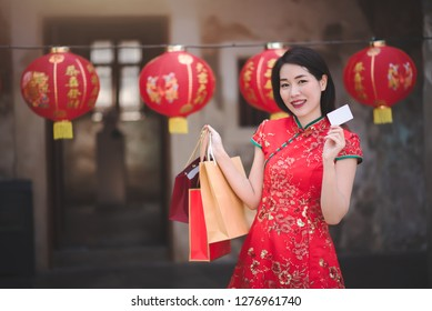 Asian Chinese Woman in Cheongsam Traditional Red Dress Holding Shopping Bag and Paid Via Credit in Chinese Lunar New Year Festival