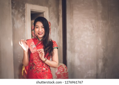 Asian Chinese Woman in Cheongsam Traditional Red Dress Holding Red Envelope for Giving Ang Pao in Chinese New Year