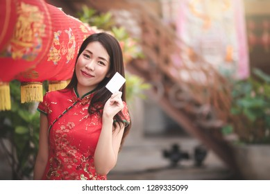 Asian Chinese Woman in Cheongsam Traditional Red Dress Holding Blank Credit for Shopping in Chinese Lunar New Year Festival