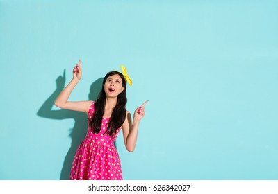 asian chinese woman pointing to the top blue background with blank copyspace and happy to imagine all the inspiration ideas with colorful clothing a lovely dress and wearing a bowknot decoration.