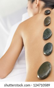 An Asian Chinese woman relaxing at a health spa while having a hot stone treatment or massage