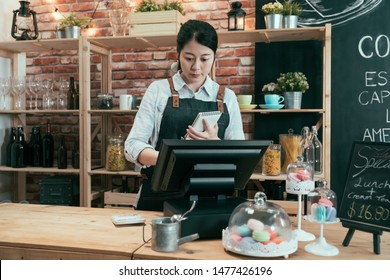 asian chinese woman rendering account with access point of sale terminal machine in coffee shop. elegant female waitress in apron holding note of customer order and touching on cash register in cafe