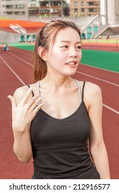 Asian Chinese woman at stadium relaxing after race