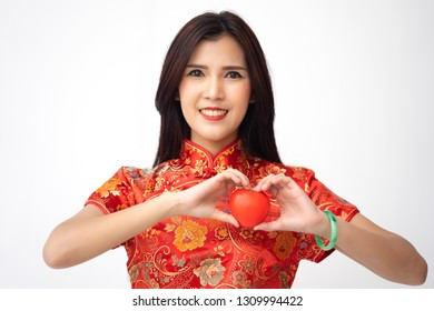 Asian Chinese woman in traditional dress giving red heart with love, persuade to take care body healthy, prevent from heart attack and performing cardio exercise to make a strong health