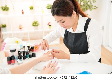 asian chinese women hands receiving a manicure. nail filing close up selective focus of nail salon, spa treatments. beauty and fashion concept.