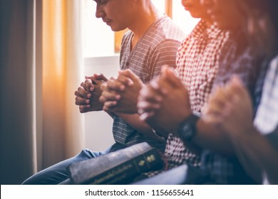 Asian Christian groups sitting within the Church Catholic. They clasped hands and closed his eyes and prayed for blessings from God. A pale sun shone in a place of worship. Everyone smiled happily.