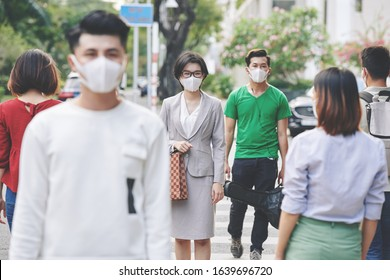 Asian citizens walking in protective medical masks in the street during coronavirus epidemic