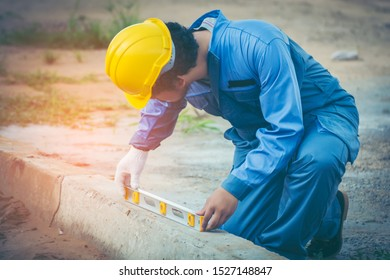 Asian civil engineer with Beard He wears the blue uniform worker and wears a yellow safety helmet. Using a plane measuring the pavement for road construction.