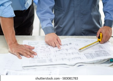 Asian Civil engineer and Asian foreman working on blueprint. Architects workplace - architectural project, blueprints, ruler, calculator, and divider. Construction concept. Engineering tools