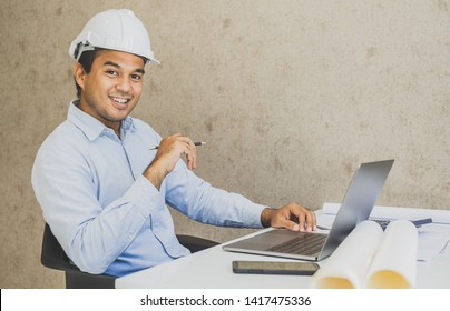 Asian civil engineer working planning project with laptop.