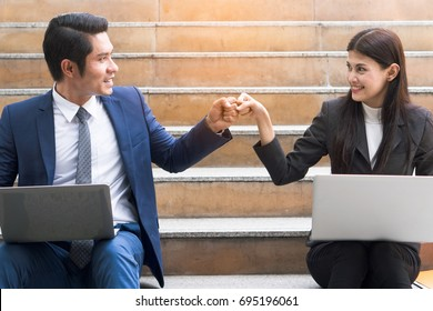 Asian colleagues team success concepts, Businessman and businesswoman looking at each other and doing fist bump celebrate after work done complete.