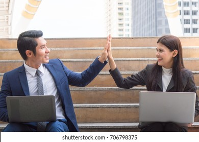 Asian colleagues team success concepts, Businessman and businesswoman looking at each other and doing high five celebrate after work done complete.